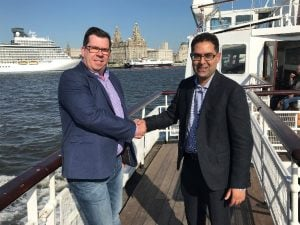 Aqualogic MD, Ben Rice and Trimble sales director, Saad Latif, shake hands on the mutual company agreement while sailing across the Mersey.
